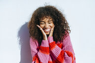Portrait of laughing young woman with curly hair against white wall - KIJF02132