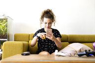 Portrait of girl sitting on the couch at home using smartphone - ERRF00057