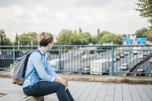 Woman with backpack sitting on motorway bridge - MOEF01487