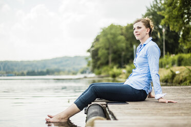 Woman sitting on jetty at a lake with feet in water - MOEF01493