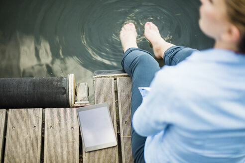 Woman sitting on jetty at a lake next to tablet with feet in water - MOEF01496
