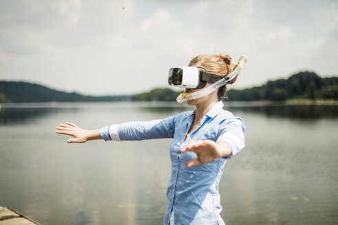 Woman with VR glasses and snorkel on jetty at a lake - MOEF01499