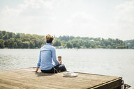 Woman sitting on jetty at a lake with headphones and takeaway coffee - MOEF01502