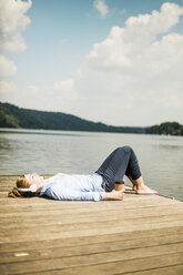 Woman lying on jetty at a lake with headphones and takeaway coffee - MOEF01505