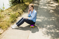 Smiling woman sitting on penny board talking on cell phone - MOEF01508