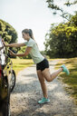 Sportive young woman stretching and using cell phone at a car in a park - MOEF01511