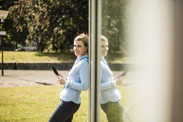 Smiling woman leaning against glass front holding tablet - MOEF01514