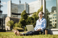 Woman wearing headphones sitting on urban meadow using laptop - MOEF01517