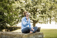 Smiling woman sitting in urban park talking on cell phone - MOEF01520