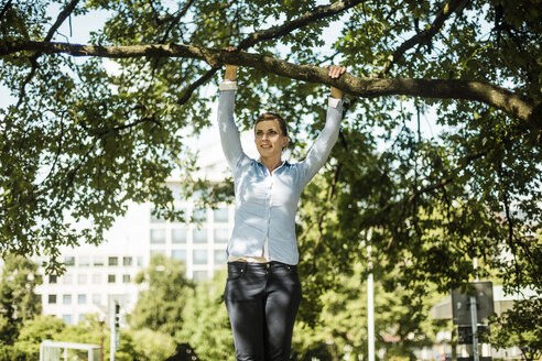 Woman in urban park hanging at branch of a tree - MOEF01523
