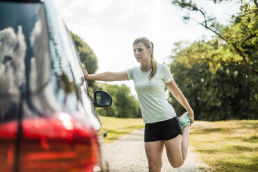 Sportive young woman stretching at a car in a park - MOEF01526