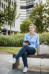 Woman sitting on a bench holding tablet - MOEF01532