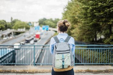Rear view of woman with backpack on motorway bridge - MOEF01535