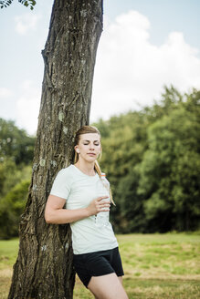 Sportive young woman leaning against a tree in a park holding bottle - MOEF01538