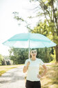 Sportive young woman standing in a park holding sunshade - MOEF01547
