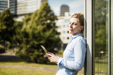 Woman leaning against a building holding tablet - MOEF01550