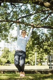 Woman in urban park hanging at branch of a tree - MOEF01553