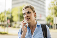 Portrait of woman with backpack in the city talking on cell phone - MOEF01556