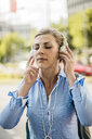 Woman with closed eyes wearing headphones in the city - MOEF01559