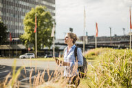 Woman with backpack and tablet in the city - MOEF01562