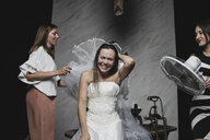 Girlfriends helping bride with preparations for her wedding celebration - KMKF00618