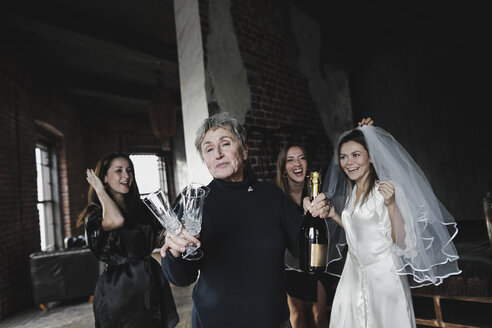 Bride's mother, bridesmaids and bride drinking champagne together - KMKF00627