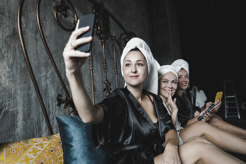 Three women with towels around her heads on bed taking a selfie - KMKF00633