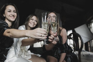 Three happy women sitting on bed clinking champagne glasses - KMKF00636