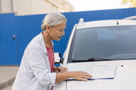 Senior woman looking at road map on  her car bonnet - VGF00103