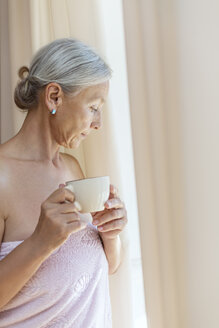 Senior woman wrapped in towel drinking cup of coffee in the morning - VGF00109
