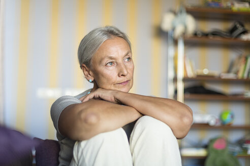 Portrait of pensive senior woman sitting on the couch at home - VGF00118