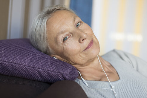Portrait of smiling senior woman lying on the couch at home listening music with earphones - VGF00121