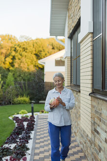 Smiling senior woman with harvested pumpkin in the garden - VGF00133
