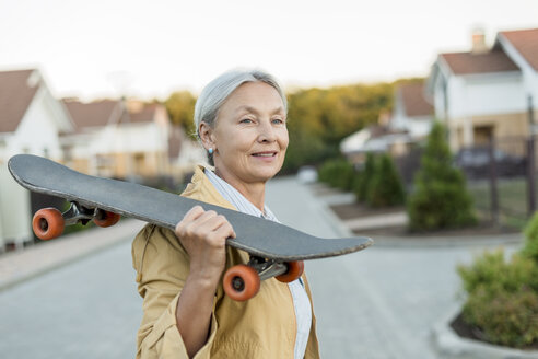 Portrait of smiling senior woman with skateboard on her shoulder - VGF00136