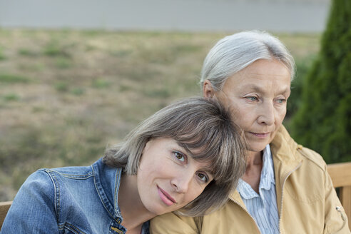 Portrait of mature woman sitting on bench with her mother outdoors - VGF00139