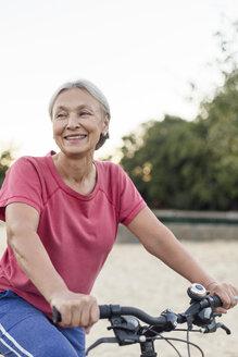 Portrait of smiling senior woman riding bicycle - VGF00142