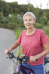 Portrait of senior woman with bicycle - VGF00145