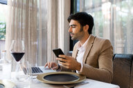 Man sitting at table in a restaurant using laptop and cell phone - VABF01645