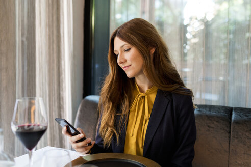 Woman sitting at table in a restaurant using cell phone - VABF01648