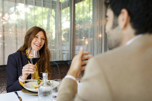 Smiling woman with glass of red wine looking at man in a restaurant - VABF01654