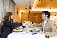 Smiling man and woman shaking hands in a restaurant - VABF01657