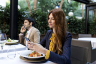 Man and woman using cell phones in a restaurant - VABF01666