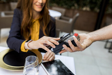 Woman paying with smartphone in a restaurant - VABF01672