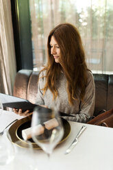 Woman sitting at table in a restaurant reading menu - VABF01678