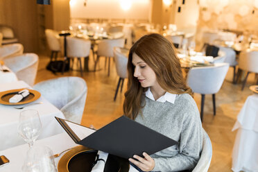 Woman sitting at table in a restaurant reading menu - VABF01681