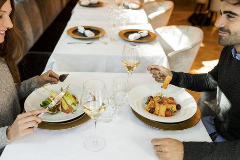 Smiling couple eating starter in a restaurant - VABF01693