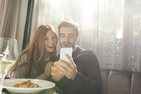 Happy couple looking at cell phone in a restaurant - VABF01696