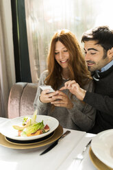 Happy couple using cell phone in a restaurant - VABF01699