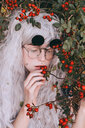 Fashion shot of woman posing with red leafy plants - INGF06955