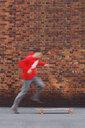 Boy jumping on his longboard against brick wall. - INGF07023